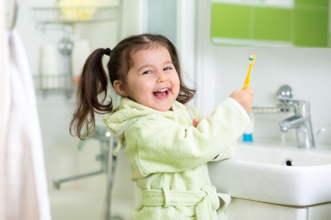 37099463 - kid little girl brushing teeth in bath