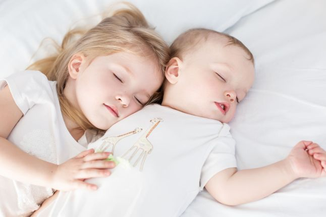 Girl and baby sleeping together