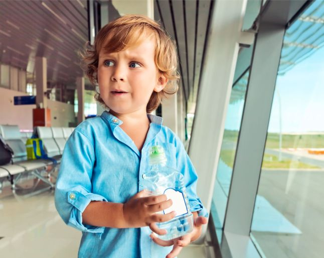 55134215 - portrait of a boy with a bottle of water in his hands at the airport