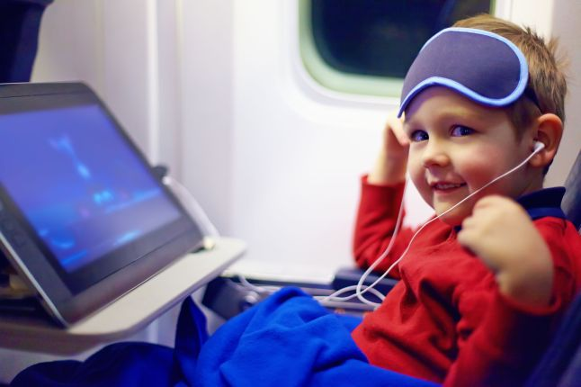 40380868 - cute little kid watching cartoons during the long flight in airplane