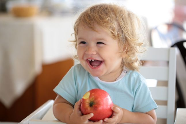 Laughing kids eating apple